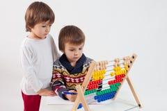 两个逗人喜爱的男孩,学会计数和算术 免版税库存照片