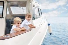 两个逗人喜爱的白种人白肤金发的男孩在船上白色豪华游艇在明亮的夏日 获得的兄弟姐妹学会乘快艇的乐趣 免版税库存照片