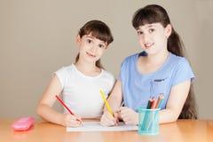 两个逗人喜爱的矮小的学校女孩画 库存照片