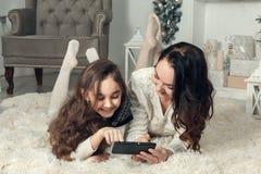 两个逗人喜爱的说谎在一个地板上的女孩、母亲和女儿在Christma 免版税库存图片