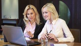 两个逗人喜爱的金发碧眼的女人谈论工作问题 图库摄影
