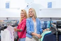 两个金发碧眼的女人妇女适合五颜六色的礼服,愉快的微笑的女孩顾客时尚商店的购物购买选择衣裳 库存照片