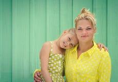 两个金发碧眼的女人妈妈和女儿微笑,拥抱 免版税库存图片