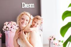 两个金发碧眼的女人-妈妈和女儿在屋子里 免版税库存图片