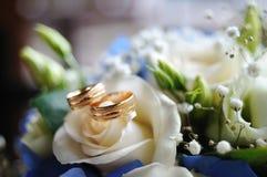 两个金子婚戒在一朵白色玫瑰说谎 免版税库存照片