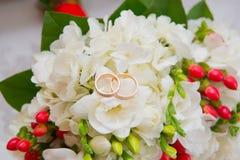 两个金子婚戒在与白花和红色莓果的花束说谎 库存照片