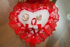 两个金子婚戒在坐垫说谎以与一根红色鞋带的心脏的形式 库存照片