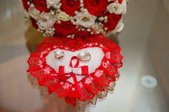 两个金子婚戒在坐垫说谎以与红色和白玫瑰红色鞋带花束的心脏的形式  免版税库存照片