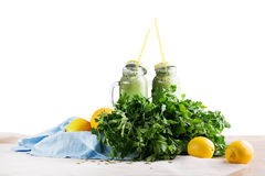 两个金属螺盖玻璃瓶从草本和菜的绿色圆滑的人,隔绝在白色背景 节食和健身概念 库存图片