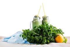 两个金属螺盖玻璃瓶从草本和菜的绿色圆滑的人,隔绝在白色背景 节食和健身概念 库存照片