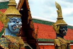 两个金黄监护人雕象在大厦ot前面安置了皇家盛大宫殿在曼谷,泰国 库存图片