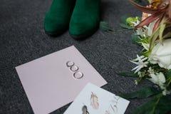 两个银婚圆环和一个定婚戒指在信封 绿色新娘鞋子、婚礼花束的部分和婚礼compl 免版税库存照片