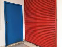 两个门紧挨着,人的小蓝色木门能使用大红色金属门为大材料 免版税库存照片