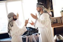 两个阿拉伯商人争论在窗口后在旅馆客房 图库摄影