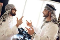 两个阿拉伯商人争论在窗口后在旅馆客房 免版税库存照片