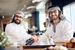 两个阿拉伯商人在旅馆客房握手在棋枰后的 免版税图库摄影