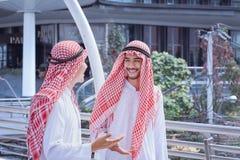 两个阿拉伯商人在现代附近一起谈论并且走 免版税图库摄影