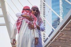两个阿拉伯商人招呼与拥抱,在城市 免版税图库摄影