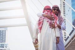 两个阿拉伯商人招呼与拥抱,在城市 免版税库存照片