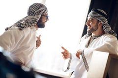 两个阿拉伯商人讲话在窗口后在旅馆客房 免版税库存照片