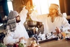 两个阿拉伯商人高五在旅馆客房的棋枰后 免版税图库摄影