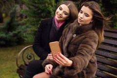 两个青少年的女孩采取与智能手机的selfie 图库摄影