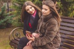 两个青少年的女孩采取与智能手机的selfie 免版税库存图片