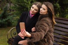 两个青少年的女孩采取与智能手机的selfie 免版税图库摄影