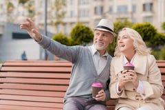 两个领抚恤金者在他们的手上坐与一杯的一条长凳咖啡 人向前显示妇女某事 免版税库存照片