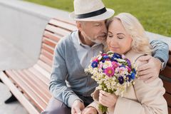 两个领抚恤金者坐在正方形的一条长凳 他们拥抱 妇女有花花束在她的手 库存图片