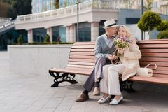 两个领抚恤金者坐在正方形的一条长凳 他们拥抱 妇女有花花束在她的手 免版税库存照片