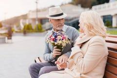 两个领抚恤金者坐在胡同的一条长凳 一个年长人给妇女花 图库摄影