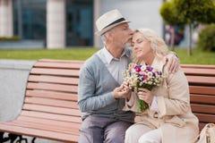 两个领抚恤金者坐在胡同的一条长凳 一个年长人轻轻地亲吻前额的一名妇女 库存图片