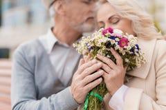 两个领抚恤金者坐在胡同的一条长凳 年迈的人给了妇女花 他握她的手 库存图片