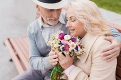 两个领抚恤金者坐在胡同的一条长凳 年迈的人给了妇女花 他握她的手 免版税库存图片