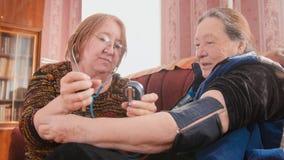 两个领抚恤金者-检查健康状态与测压器-措施压力,领抚恤金者医疗保健 库存图片