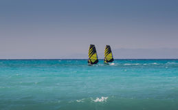 两个风帆冲浪者在海乘坐平行 库存照片