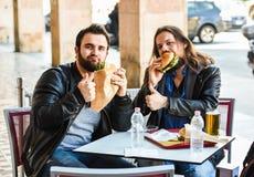 两个饥饿的朋友/游人吃着与赞许的汉堡包 免版税库存照片