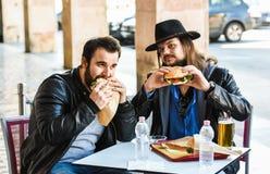 两个饥饿的朋友/游人吃着汉堡包 免版税库存照片