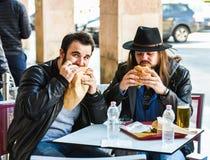 两个饥饿的朋友/游人吃着汉堡包 免版税库存图片