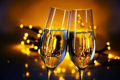两个香槟槽使玻璃叮当响在圣诞节或新年的p 免版税库存图片