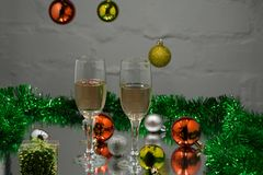 两个香槟玻璃、圣诞树、圣诞节礼物和圣诞节球在黑背景 免版税库存照片