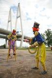 两个马戏团小丑设计卡通者投掷色的圆环 免版税库存照片