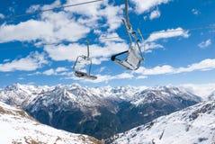 两个驾空滑车位子互相反对在冬天风景 免版税库存图片