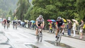 两个骑自行车者乘坐在雨中的-环法自行车赛2014年 免版税库存图片