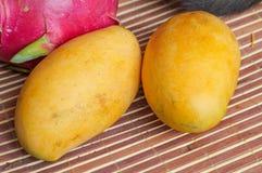 两个黄色成熟芒果和龙果子 库存图片
