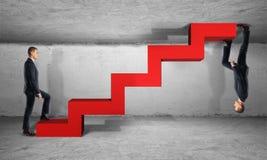 两个从不同的边的商人攀登一红色梯子 免版税库存照片