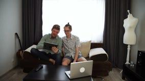 两个年轻人兄弟从坐长沙发和运作在他的片剂的家工作,在桌膝上型计算机 股票录像