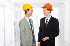 两个年轻人商人佩带的安全帽 图库摄影