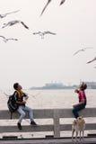 两个年轻人在天空中的喂养鸟在轰隆Pu海边 免版税库存图片